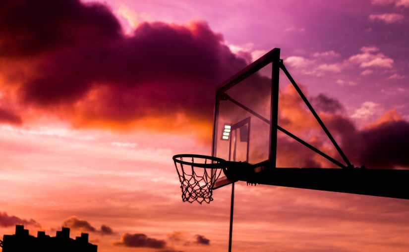 silhouette photo of basketball hoop during golden hour